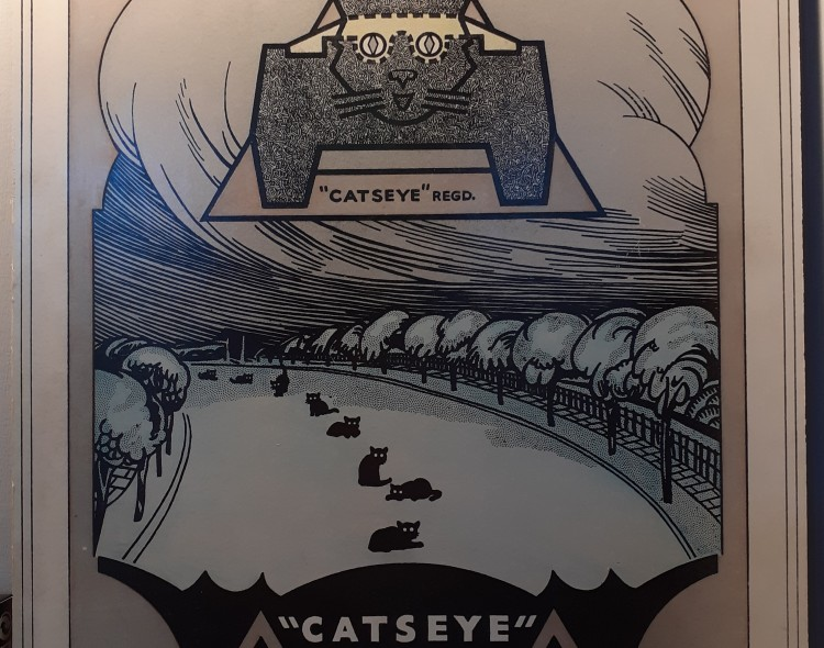 A poster showing a series of black cats sitting down the middle of a road with the text 'catseye self-wiping reflecting road studs'
